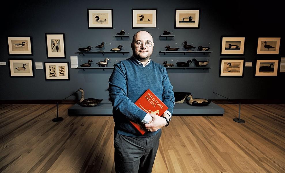 "Kory Rogers standing in front of the ""Joel Barber & the Modern Decoy"" exhibit - BEAR CIERI"