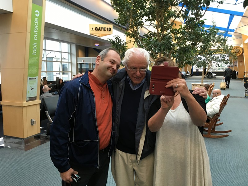 Sen. Bernie Sanders poses for selfies at Burlington International Airport Friday on his way to a debate in Des Moines. - PAUL HEINTZ