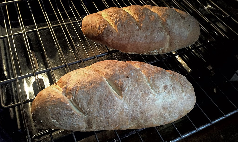 Loaves of hearth bread coming out of the oven - MARY ANN LICKTEIG