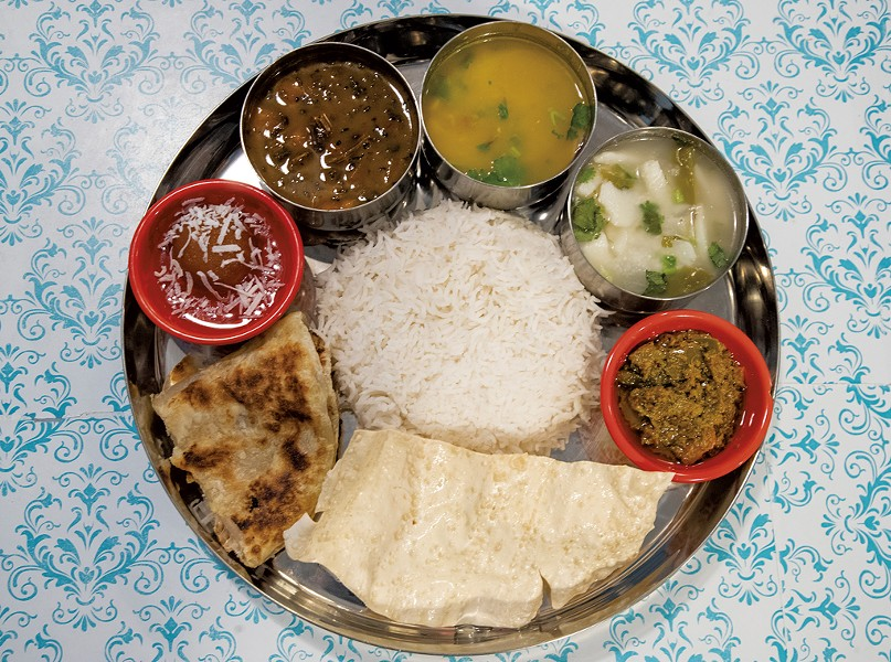 House special thali (clockwise from top left): gundruk soup, lentil soup, ema datshi, mango chutney, two breads, gulab jamun and rice from Friend's Nepali Restaurant - JAMES BUCK