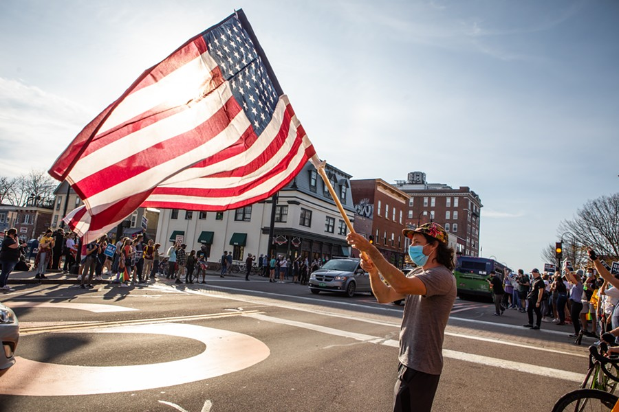 A man waving a flag to passing vehicles in downtown Burlington - LUKE AWTRY