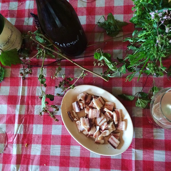 A bottle of Ci Confonde and Caleb Barber's homemade pancetta - JULIA CLANCY
