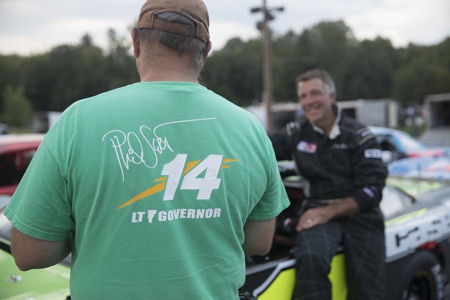 Crew member Jim Morrill talks to Lt. Gov Phil Scott before Scott's race at Thunder Road in Barre on Thursday, Aug 11. - JAMES BUCK