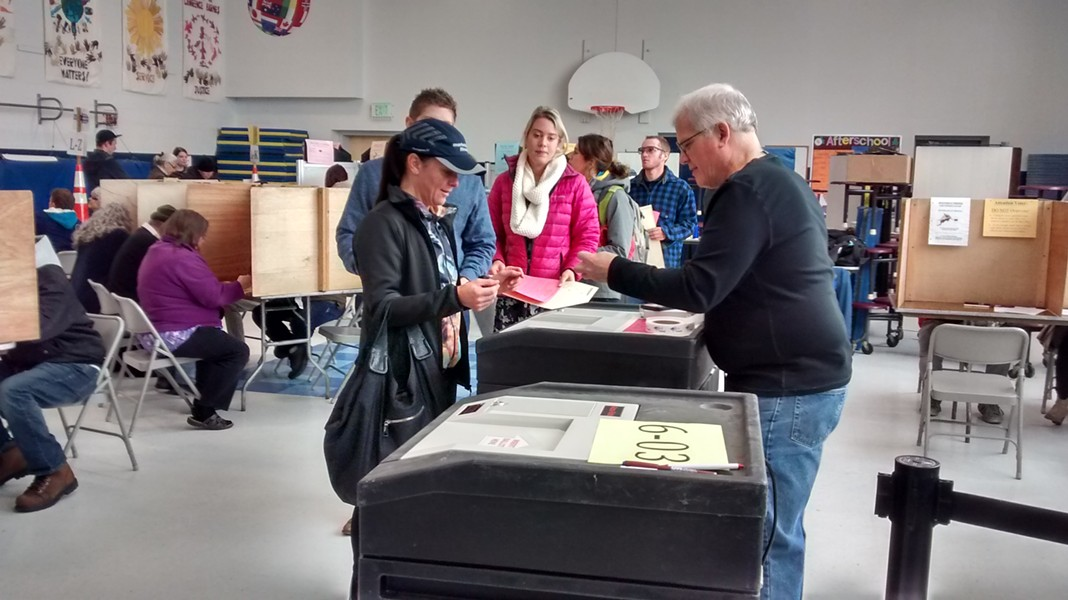 Voters line up to cast their ballots at the Sustainability Academy at Lawrence Barnes. - KATIE JICKLING