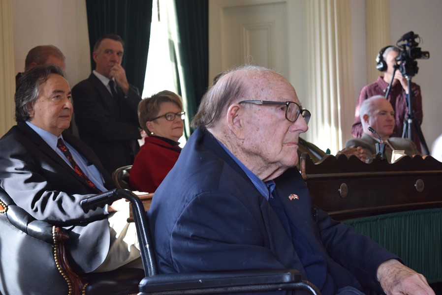Bill Doyle listens as senators honor him, while Gov. Phil Scott looks on. - TERRI HALLENBECK