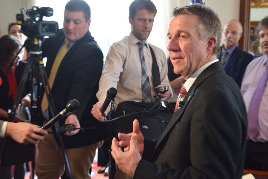 Gov. Phil Scott discusses health care negotiations with reporters Friday in his Statehouse office. - TERRI HALLENBECK