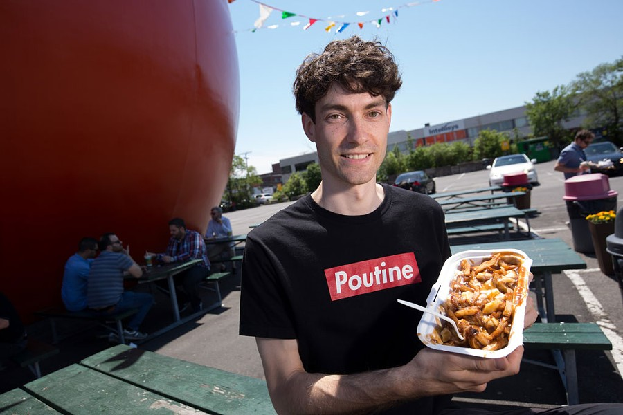 Nicolas Fabien-Ouellet, a student in the University of Vermont's Food Systems Master's program, with an order of poutine from Orange Jules in Montreal. - OWEN EGAN