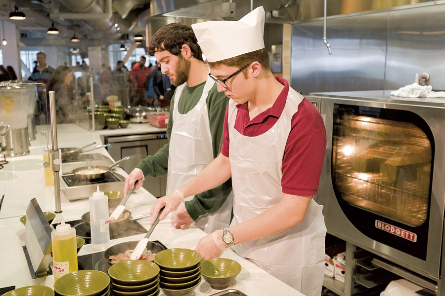 UVM students Julian Wagner (right) and Nicholas Vartanian cooking for themselves in the Central Campus Dining Hall - OLIVER PARINI