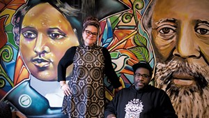 "Jennifer Herrera Condry and Will ""KASSO"" Condry in front of a mural depicting Mary Annette Anderson and Martin Henry Freeman"
