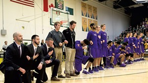 Saint Michael's College men's basketball players kneel during the anthem in an exhibition game at the University of Vermont