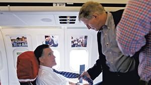 Mitt Romney (left) and Stuart Stevens talking aboard the Romney campaign plane in October 2012