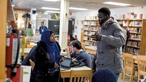 Yuol Herjok of Spectrum Youth & Family Services (right) speaking with Burlington High School senior Halima Said at the school's Spectrum Multicultural Help Desk