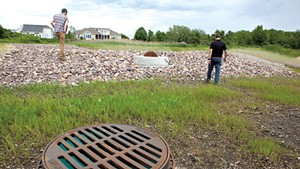 David Wheeler (left) and Tom DiPietro touring a  rebuilt stormwater pond at the Pinnacle at Spear neighborhood