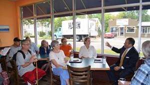 Burlington Police Chief Brandon del Pozo addressing residents at the Bagel Cafe & Deli