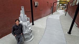 "Sean Hunter Williams with his granite sculpture ""Culmination"""