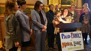 Christine Vance holding her son, Ben, as she addresses supporters of paid family leave in the Statehouse on Wednesday