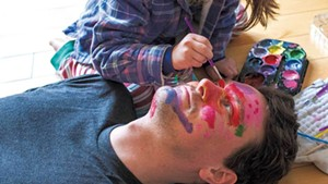 Torrey Valyou gets his face painted by 5-year-old daughter Lily at their home in Burlington