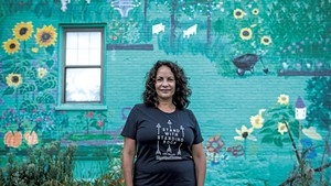 Gina Carrera standing in front of her mural on South Champlain Street