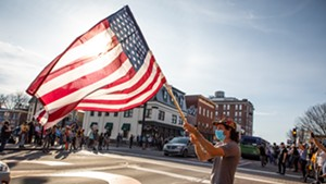 A man waving a flag to passing vehicles in downtown Burlington