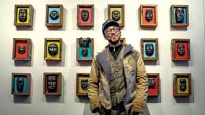 Harlan Mack posing in front of some of his work in a coat and vest he sewed himself at his studio in Johnson