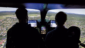 Beta Technologies CEO Kyle Clark operating the company's flight simulator with reporter Derek Brouwer