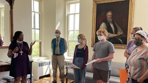 Bishop Shannon MacVean-Brown speaking with students in front of the portrait of John Henry Hopkins that has been removed