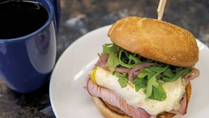Breakfast sandwich with ham, arugula and pickled red onions