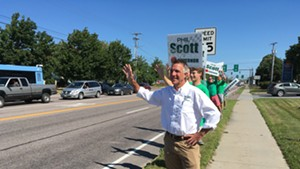 Phil Scott waves to passersby on Shelburne Road in South Burlington on Monday.