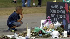 A young boy at the Michael Brown memorial site in Ferguson, Mo.