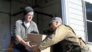 Chef and farmer Joe Buley handing off a soup order to Gregory Georgaklis