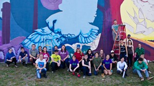 Champlain College students in front of their mural with Anthill Collective