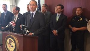 U.S. Attorney Eric Miller, at podium