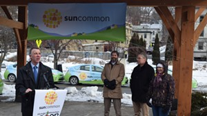 Gov. Phil Scott (left) joins SunCommon cofounder (second from left) James Moore at a press conference Monday.