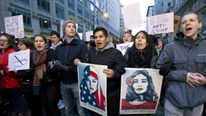 Demonstrators march on the street near a security checkpoint inaugural entrance.