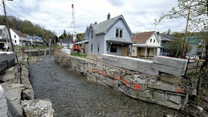 Flood-damaged homes and flood-control pylons in Gunners Brook in Barre