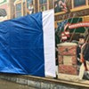 """A tarp covers the vandalized section of the """"Everyone Loves a Parade!"""" mural in Burlington."""