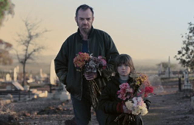 Weaving and Russell are stealing those cemetery flowers in Last Ride