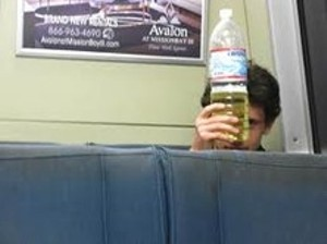 A BART commuter holds a bottle full of God knows what