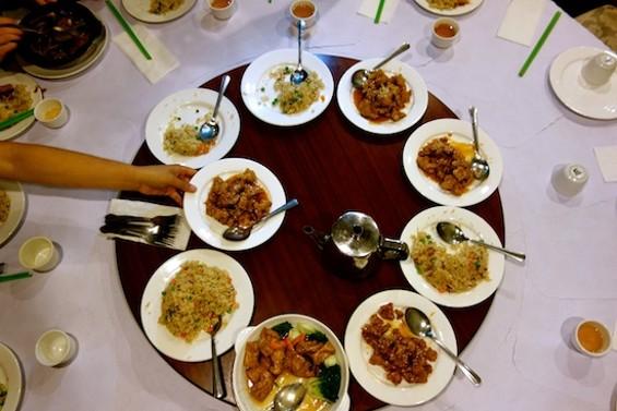 A diner reaches for the veggie sesame chicken at Natural Vegetarian Restaurant - FERRON SALNIKER