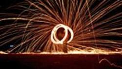 JULIAN  CASH - A fire performer lights up the night sky.