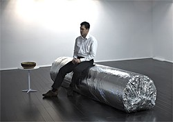 A spectator sits on a super burrito bench.