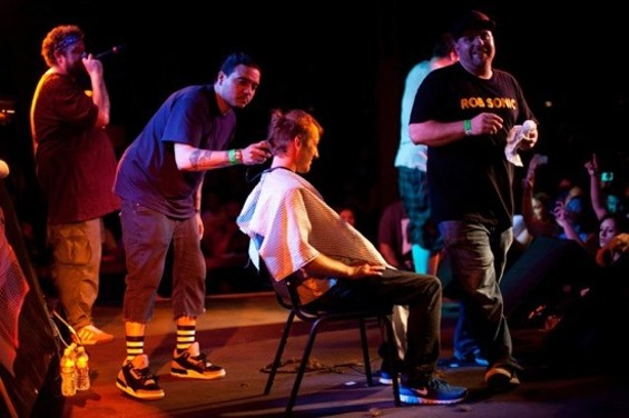 A voluntary victim gets a haircut onstage in San Diego