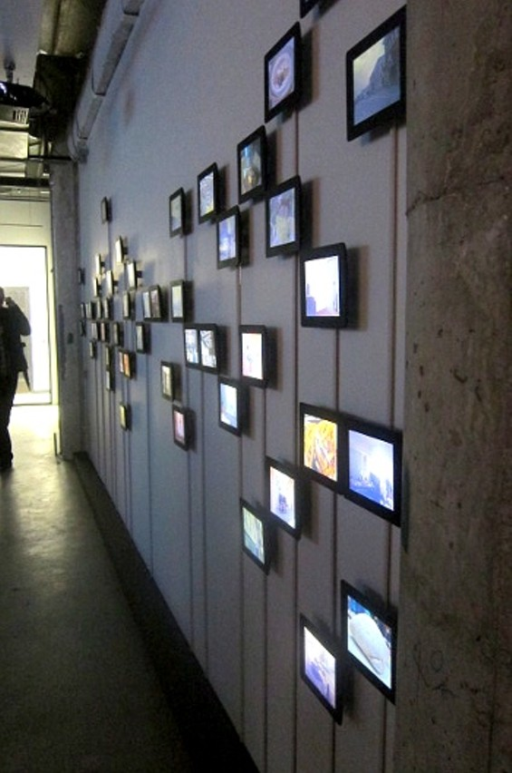 A wall of monitors displays the thousands of photos Elahi shot since 2002 documenting his own whereabouts.