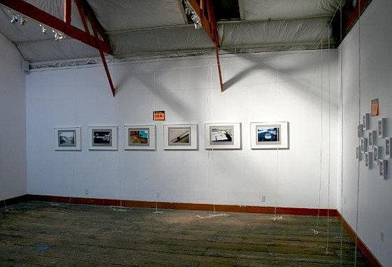 All is calm before the first visitor arrives. Framed photographs line one wall, small framed drawings another.