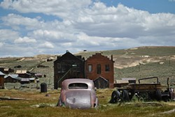 PHOTOGRAPHS BY ERIN SHERBERT - An abandoned and rusted car sits outside a field flanked by historic buildings in Bodie, Calif.