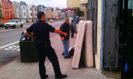 An officer asks Dustin to lean the mattress and box spring against the wall at a sharper angle, so they don't fall onto the sidewalk - JOE ESKENAZI