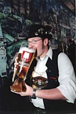 An Oktoberfest celebrant demonstrates proper - brew-swilling form.