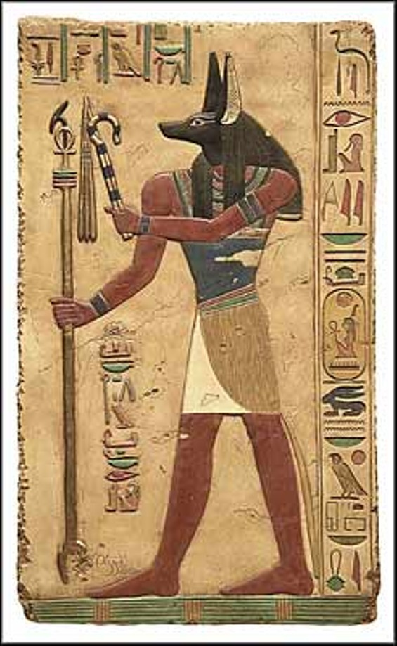 Anubis relief: He carries the long 'was' scepter and the crook and flail, symbols of kingship.