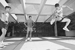 "PAOLO  VESCIA - As the Disco Ninja (left) and Sunil ""Tsunami"" Jani look - on, Tu Vu, Tuan's brother, elevates for a tough trick - during practice."