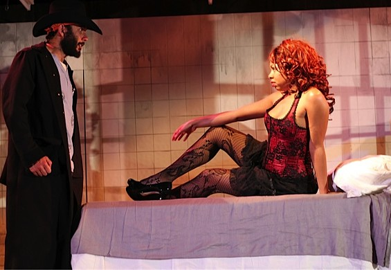 At a brothel, Drumhead (Wiley Naman Strasser) approaches Scarlett ( Felicia Benefield) in her boudoir in Cutting Ball Theater's World Premiere of Krispy Kritters in the Scarlett Night. - ROB MELROSE